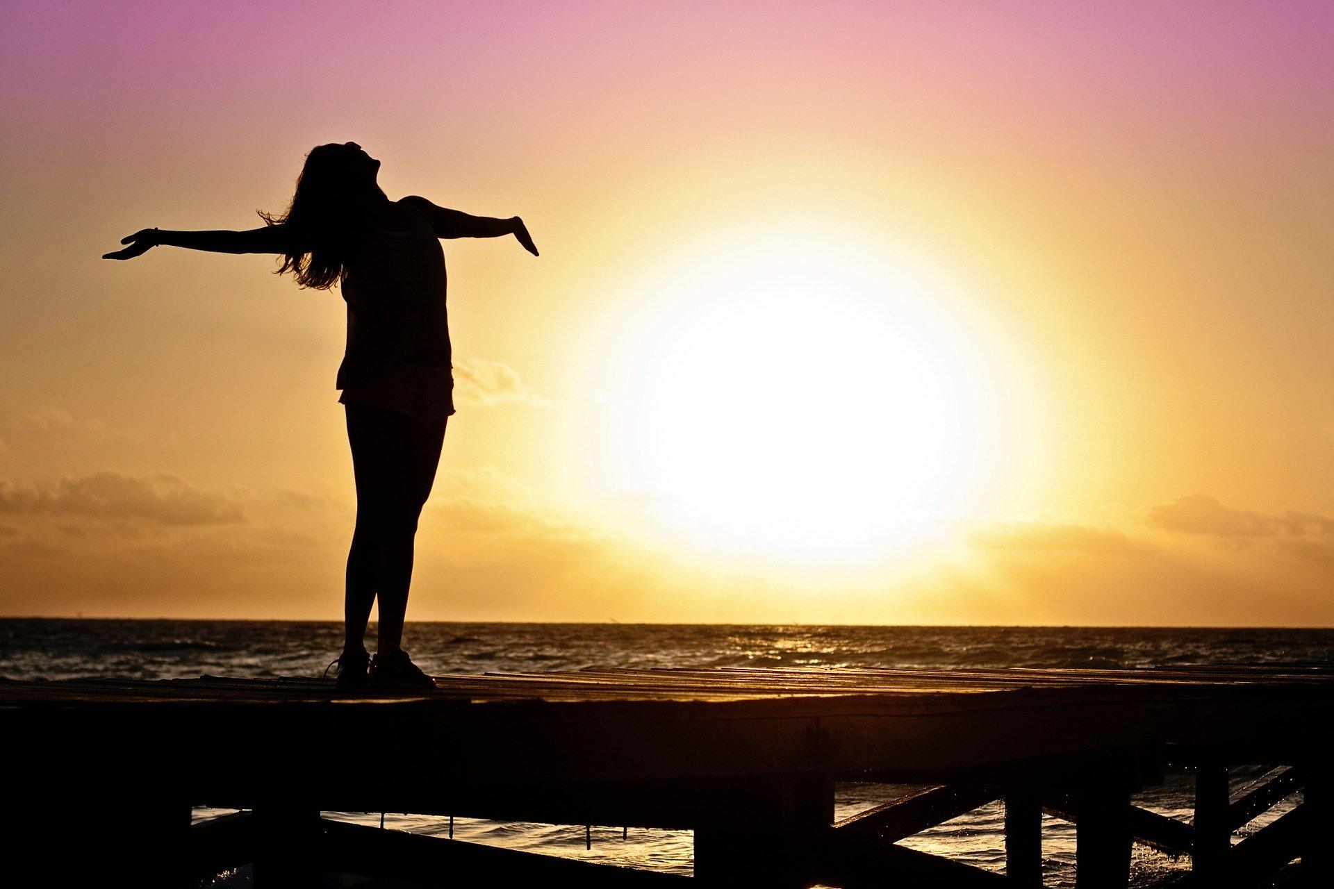 Frau im Sonnenuntergang am Meer